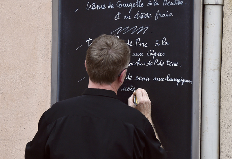A man write on a board displayed on the facade of its restaurant, the menu of the day on May 4, 2015 in the Toulouse.       AFP PHOTO / PASCAL PAVANI        (Photo credit should read PASCAL PAVANI/AFP/Getty Images)