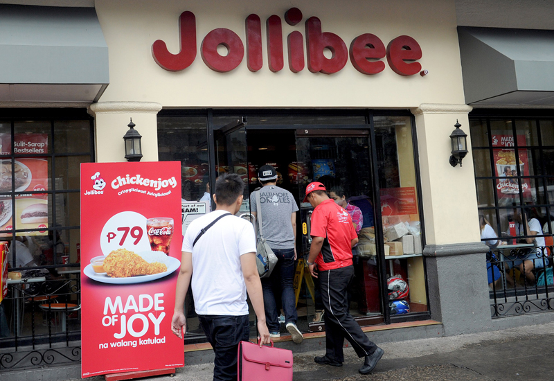 Customers enter a store of Philippines' leading fast-food giant Jollibee Foods in Manila on October 14, 2015. Jollibee Foods announced on October 13 it had acquired 40 percent of an upmarket US hamburger chain for 99 million USD.      AFP PHOTO / Jay DIRECTO        (Photo credit should read JAY DIRECTO/AFP/Getty Images)