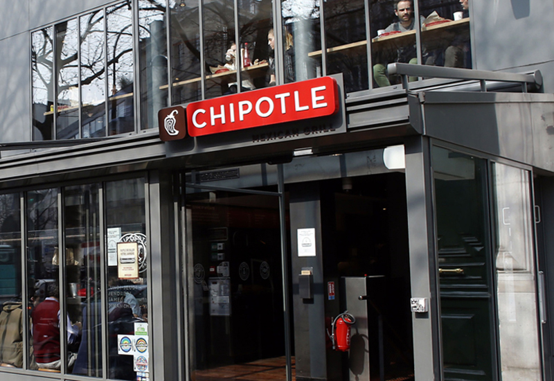 "TO GO WITH AFP STORY BY ANNE-SOPHIE MOREL People walk past the ""Chipotle"" restaurant in Paris on March 18, 2015. France has become a new hunting ground for foreign fast food brands looking to establish branches. AFP PHOTO / THOMAS SAMSON        (Photo credit should read THOMAS SAMSON/AFP/Getty Images)"