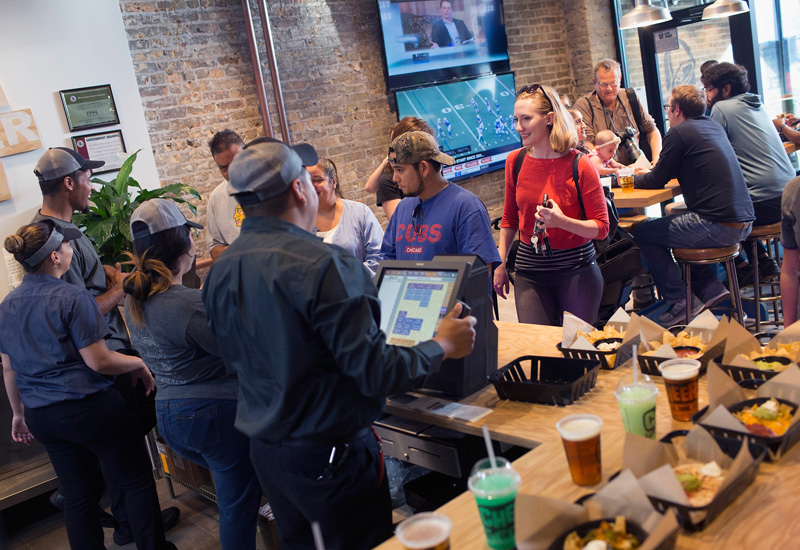 CHICAGO, IL - SEPTEMBER 22:  Worker wait on guests at a Taco Bell Cantina restaurant on September 22, 2015 in Chicago, Illinois. The restaurant is Taco Bell's first to serve alcohol. Along with the regular fast food menu guest can also order beer, wine, sangria and twisted Freezes which can be mixed with rum, tequila or vodka.  (Photo by Scott Olson/Getty Images)