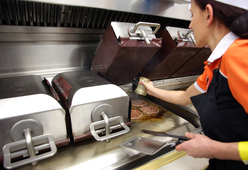 FRANKFURT AM MAIN, GERMANY - MARCH 30:  A female employee works in the kitchen at the new McDonald's Flagship Restaurant at Frankfurt International Airport, Terminal 2, on March 30, 2015 in Frankfurt am Main, Germany.  (Photo by Hannelore Foerster/Getty Images)