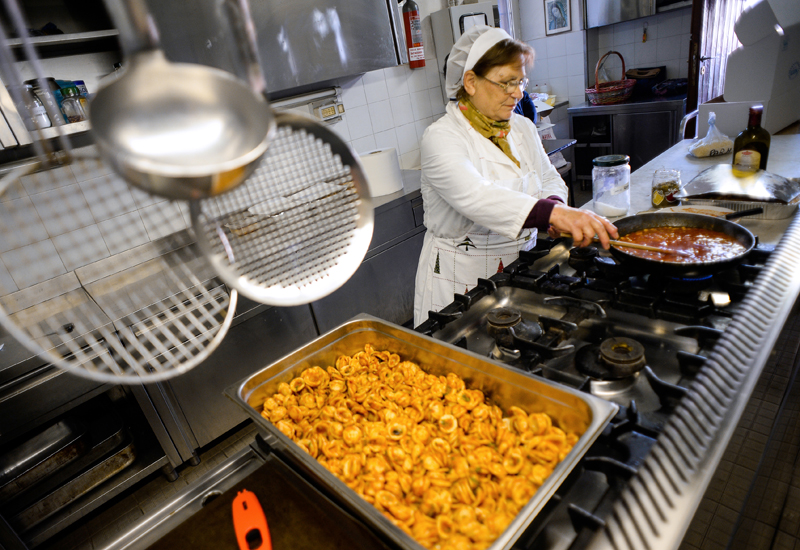 "TO GO WITH AFP STORY BY FRANCESCA CARUSO A volunteer of Caritas, a Catholic charity association, prepares meals in a kitchen of the ""St. Benedict parish"", in Rome, on May 28, 2013. As soup kitchens in Rome fill up because of rising unemployment, some of the Italian capital's most famous eateries are stepping up -- giving away day- smacking pizza and pasta dishes. Groceries and restaurants are put in touch directly with charities that need the food by a new initiative called ""Pasto Buono"" (""Good Meal"") that intends to combat the paradox of food waste and hunger by aiming to give out 110,000 meals a year in Rome.  AFP PHOTO / ANDREAS SOLARO        (Photo credit should read ANDREAS SOLARO/AFP/Getty Images)"