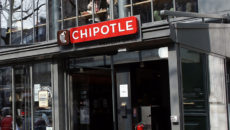"""TO GO WITH AFP STORY BY ANNE-SOPHIE MOREL People walk past the """"Chipotle"""" restaurant in Paris on March 18, 2015. France has become a new hunting ground for foreign fast food brands looking to establish branches. AFP PHOTO / THOMAS SAMSON        (Photo credit should read THOMAS SAMSON/AFP/Getty Images)"""