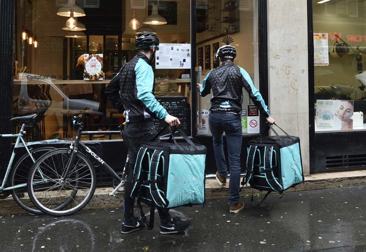 "Bikers working for Food delivery service Deliveroo enter a restaurant to pick up meals they will deliver, on March 31, 2016 in Paris. Food delivery service Deliveroo, created in 2013 in the UK and operating in France for a year, said on March 31 it had already served a "" million meals "" in France, presenting itself as the ""leader"" of this thriving market . / AFP / Eric FEFERBERG        (Photo credit should read ERIC FEFERBERG/AFP/Getty Images)"