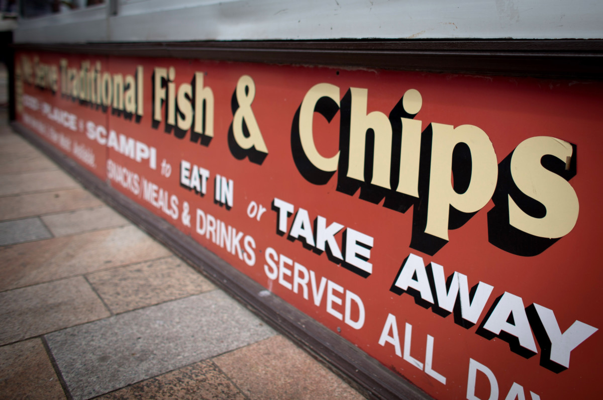 WESTON-SUPER-MARE, ENGLAND - JUNE 11: A sign outside a cafe advertises traditional fish and chips as people enjoy the fine weather on June 11, 2015 in Weston-Super-Mare, England. Many traditional British seaside resorts are gearing up for the summer season and will be hoping that the traditional attractions offered will help keep visitor numbers up. (Photo by Matt Cardy/Getty Images)
