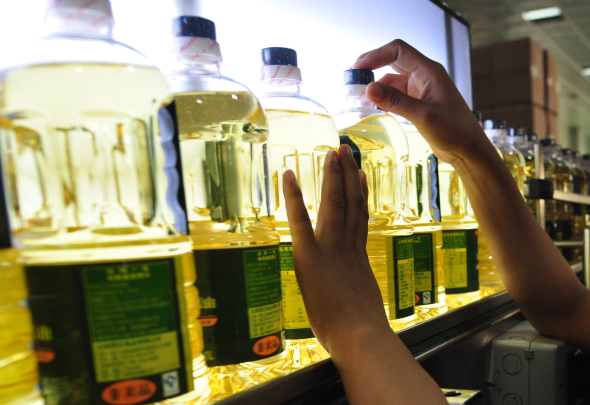 In this picture taken on May 9, 2012, a worker inspects the bottles of corn oil produced at a factory in Zouping, northeast China's Shandong province. Manufacturing activity in China contracted for the sixth straight month in April but at a much slower pace, banking giant HSBC said, lifting hopes the giant economy may have turned a corner.             CHINA OUT      AFP PHOTO        (Photo credit should read STR/AFP/GettyImages)