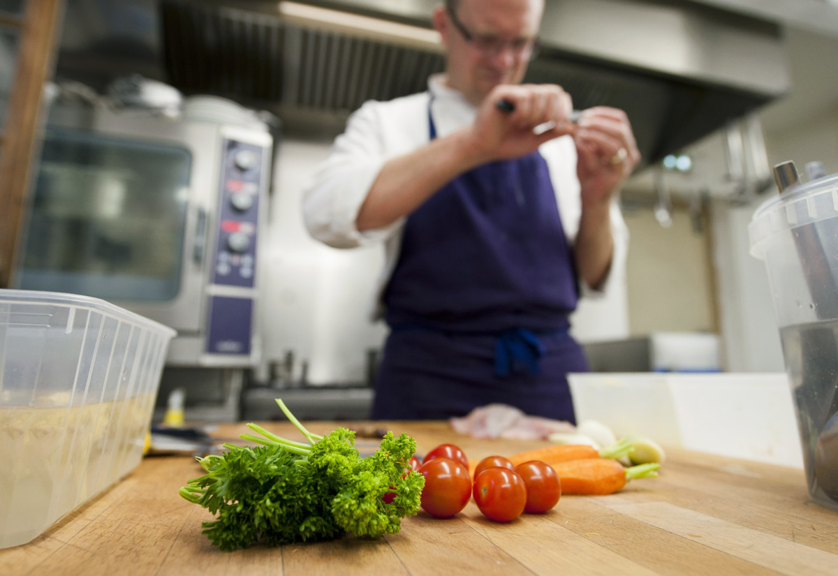 Chef in kitchen cutting vegetables